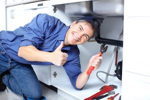 Mature plumber fixing a sink at kitchen